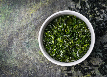 Wakame seaweed in water bowl on rustic background, top view, place for text