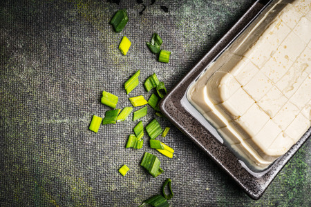 silken: Diced Silken tofu on rustic background, top view, close up