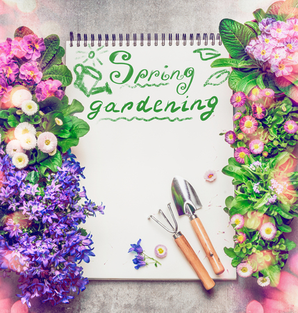 garden frame: Floral Gardening background with assortment of colorful garden flowers, paper notebook ,gardening tools and text Spring Gardening, top view, frame
