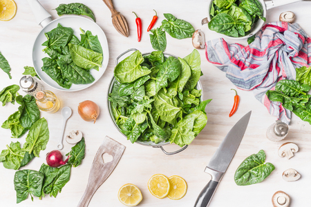 ustensiles de cuisine: Fresh green spinach leaves in colander on white kitchen table background with cooking ingredients, spoon and knife, top view