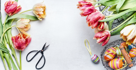 Easter workspace with colorful tulips, shears and deco eggs in basket, top view, frame Stock Photo