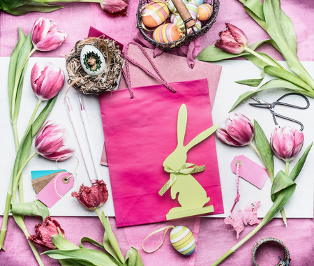 Easter workspace in pink color:  tulips flowers and accessories for easter decorations making with eggs, paper bags and basket, top view, place for text Stock Photo