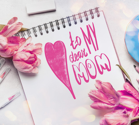 copies: Mothers Day Greeting card with text lettering To my dear mom, pale pink  tulips, notebook or sketchbook and colorful brush markers ,  top view Stock Photo