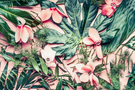tropical flowers: Creative layout made of tropical flowers and palm leaves on pastel pink background, top view,  flat lay