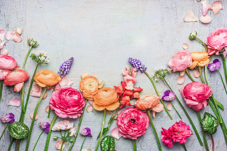 Border of Various beautiful garden flowers on shabby chic background, frame, top view, floral border
