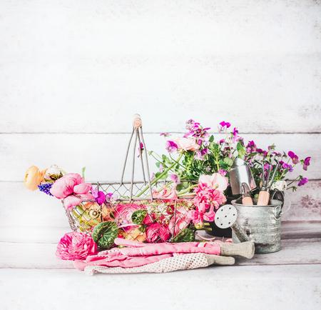 夏のガーデニングの花、園芸工具、白い木製の背景、正面で水まき缶バスケット