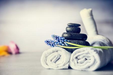 Spa-Massage-Einstellung mit Handtüchern, heißen Steinen und blauen Blumen, close up, Wellness-Konzept, Vorderansicht