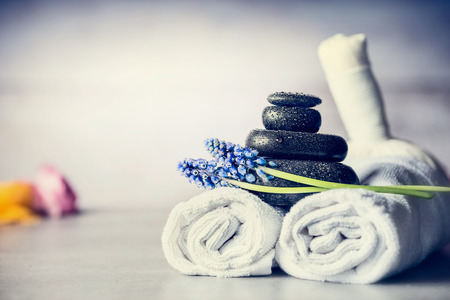 Spa massage setting with towels, hot stones and blue flowers, close up, wellness concept, front view