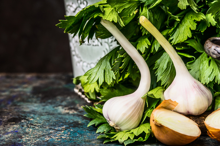 Fresh garlic on rustic wooden table at dark background, front view. Spicy Cooking concept