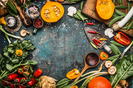 Healthy and organic harvest vegetables and ingredients: pumpkin, greens, tomatoes,kale,leek,chard,celery on rustic kitchen table background for tasty Thanksgiving seasonal cooking, frame, top view