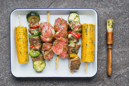 Meat, vegetables and corn skewers in green herbs rubs and marinades Stock Photo