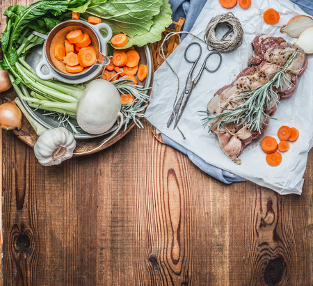 white backing: Raw Pork roast on white backing paper with vegetables and condiment, preparation on rustic wooden background, top view, border