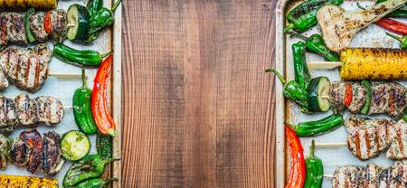 素朴な木製の背景、平面図、バナー、テキストのための場所で野菜を様々 なロースト肉串と食品の背景。肉料理、グリルのコンセプト