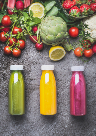 Variety of colorful Smoothies or juices beverages drinks in bottles with fresh ingredients: fruits ,berries  and vegetables on gray concrete background , top view.  Healthy Food concept