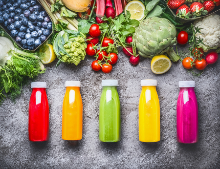 Healthy red, orange, green, yellow and pink Smoothies  and juices in Bottles on grey concrete background with fresh organic vegetables , fruits and berries ingredients, top view Stock Photo