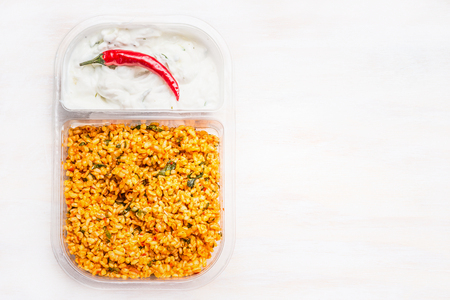 Couscous salad with yogurt dip in lunch box on white wooden background , top view