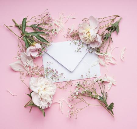 Pastel pink flowers around White envelop , floral arrangement , top view