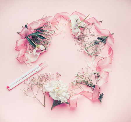Round floral frame arrangement  with pastel pink flowers, markers and ribbon, top view. Stockfoto