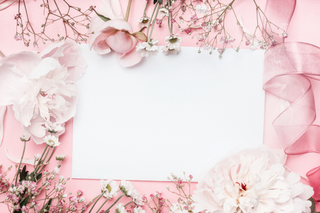White blank card with pastel flowers and ribbon on pink pale background, floral frame. Creative greeting, Invitation and holiday concept Archivio Fotografico