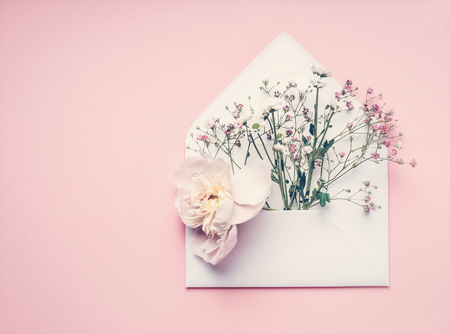 Opened envelop with flowers arrangement on pastel pink background, top view, copy space. Creative greeting, Invitation and holiday concept 스톡 콘텐츠