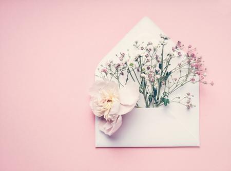 Geopend enveloppe met bloemen arrangement op pastel roze achtergrond, bovenaanzicht, kopieer ruimte. Creatieve begroeting, Uitnodiging en vakantieconcept