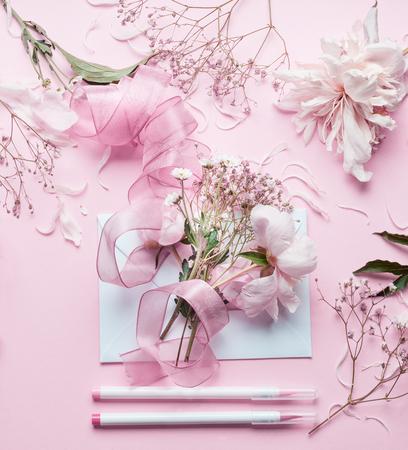 사랑스러운 핑크 꽃집 작업 영역입니다. 아름 다운 꽃, 봉투, 리본 및 표식 파스텔 배경, 상위 뷰를 연필. 크리 에이 티브 초대 및 휴일 개념