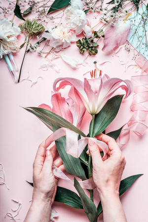 Female hands making lovely pink lily flowers bouquet on pastel female hands making lovely pink lily flowers bouquet on pastel table with florist decoration equipment mightylinksfo