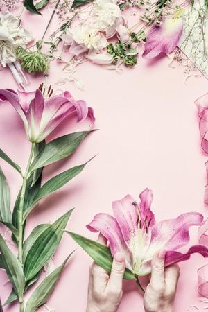 Spazio di lavoro floreale. Mani femminili in possesso di bellissimi fiori di giglio rosa sul tavolo pastello con decorazione di fiori, vista dall'alto, telaio. Disposizione Fiori creativi. Invito e festa, concetto