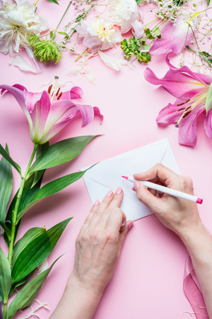 tinker: Female hands write with pencil greeting card on Blank envelop on pink table background with lily flowers and florist decoration equipment, top view. Creative  Invitation and holiday  concept