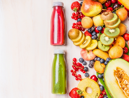 Red and green smoothies and juices beverages in bottles with various fresh organic fruits and berries ingredients on white wooden background, top view. Healthy food and vegetarian concept
