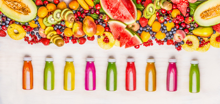 Variety of colorful smoothies and juices beverages in bottles with various fresh organic fruits and berries ingredients on white wooden background, top view. Healthy food concept