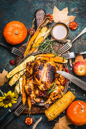 Roasted  stuffed whole turkey or chicken with organic harvest vegetables and pumpkin for Thanksgiving dinner served on rustic cutting board, top view
