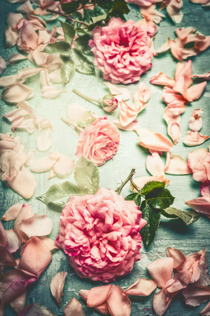 Pink roses composing with flowers petal and leaves on turquoise  shabby chic background, top view, retro toned, vertical
