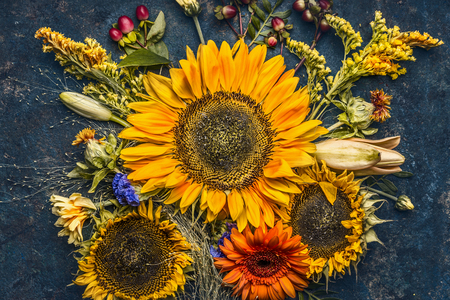 Autumn flowers and leaves composition with sunflowers on dark rustic background , top view, fall nature 版權商用圖片