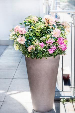 Mooie terraspot met bloemstukken: rozen, petunia's en verbena's bloeien op balkon of terras. Stedelijke Container planter tuinieren