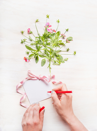 Female hand Write a greeting card on white wooden background with flowers bunch and pink ribbon, top view, copy space,  mock up Stock Photo