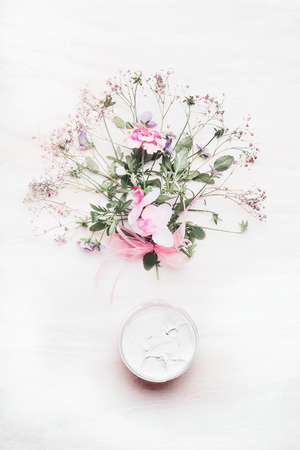 holistic view: Organic botanical cream with organic herbs and flowers bunch on white wooden background, top view. Organic herbal and botanical cosmetic,  beauty and skincare product concept Stock Photo