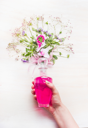 holistic view: Female hand holding bottle with pink lotion and flowers and herbs bunch on white wooden background, top view. Organic herbal and  botanical cosmetic, Perfume and beauty concept