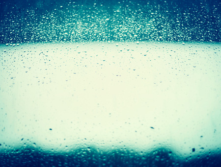Rain water drops on blue window glass background.