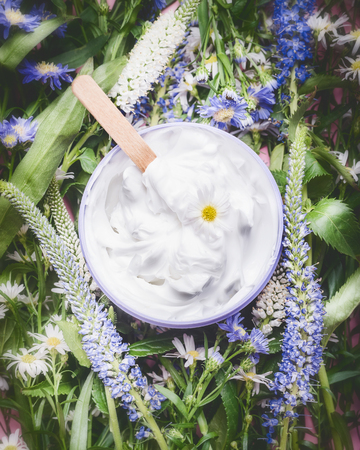 Herbal cosmetic cream with herbs and flowers , top view. Skincare product , wellness in jar. Natural cosmetic product and beauty concept