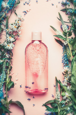 Natural Cosmetic product bottle on pink pale background with plant and flowers, top view, copy space. Floral cosmetics, botanical fragrance concept.