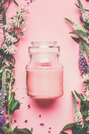 Jar of pink natural cosmetic cream with flowers and herbs, top view. Natural herbal cosmetic product and beauty concept