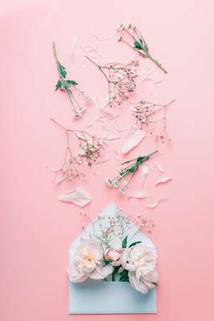 Opened envelope with pastel flowers and petals on pink pale background, top view, flat lay Stock Photo