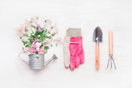 女性園芸ワークスペース、白い木製の背景、平面図、平面レイアウトにじょうろで花とガーデン ツール
