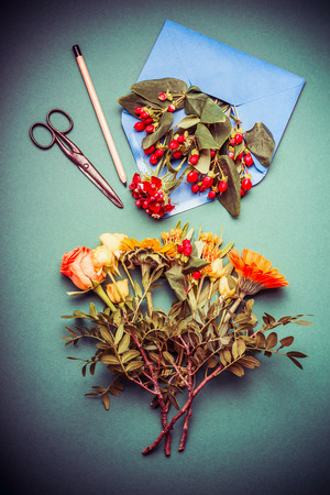 Autumn  flowers arrangements making on table workspace with scissors , envelope and ribbon, top view