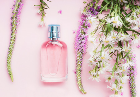 Floral perfume bottle with fresh herbs and flowers on pink background, top view.  Beauty concept