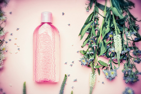 Plastic bottle with tonic or micellar cleansing water with fresh herbs and flowers on pink background, top view.  Beauty, skin, hair or body care concept