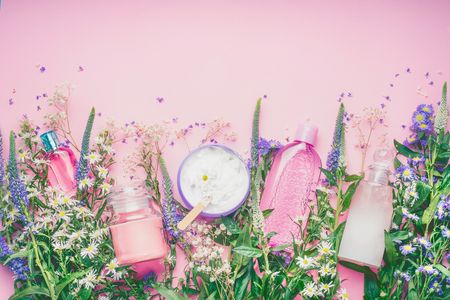 Natural cosmetic products setting with fresh herbs and flowers on pink background, top view, border. Beauty, skin or body care concept