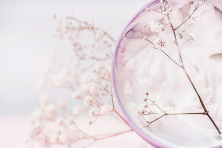 Close up of Jar with cosmetic cream and flowers , natural cosmetic product or beauty concept on pastel background, front view