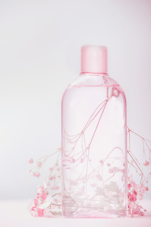Bottle with lotion, tonic or micellar cleansing water , natural cosmetic product or beauty concept on pastel background, front view 写真素材